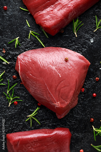 Canvas Print Raw venison steak with rosemary and pepper on black rustic table.