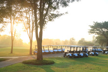 Golf Carts On A Beautiful Golf Course At The Sunset, Sunrise Time.
