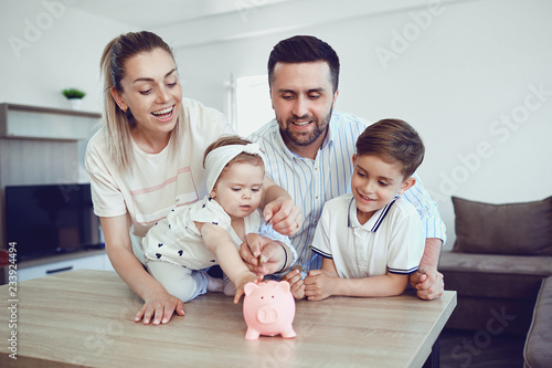 Fototapeta A smiling family saves money with a piggy bank.