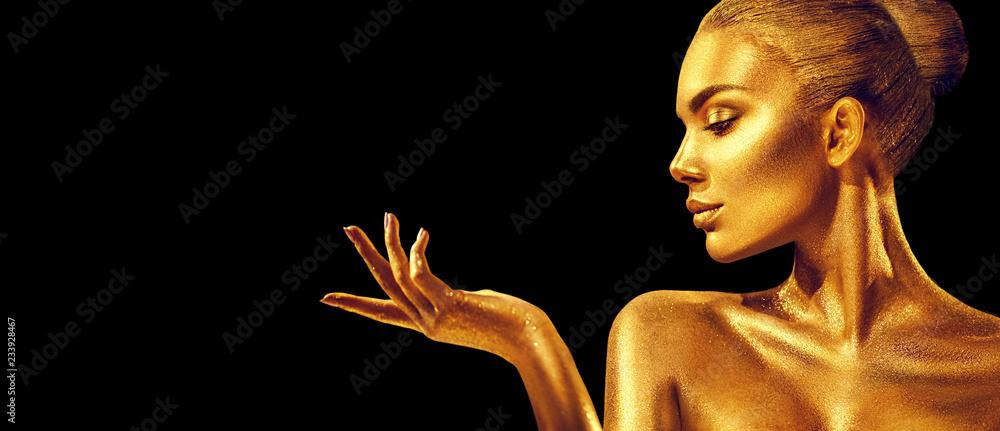 Fototapeta Golden woman. Beauty fashion model girl with golden skin, makeup, hair and jewellery on black background. Fashion art portrait