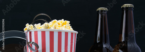 film in popcorn, on a black background, with two bottles of beer
