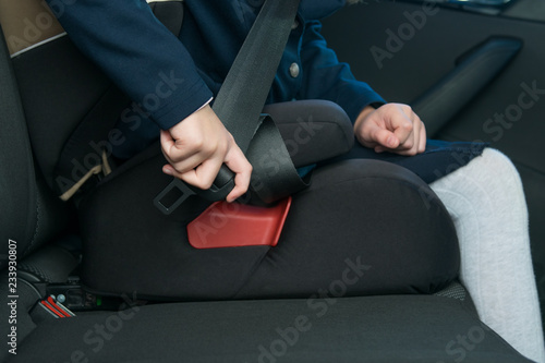Photo  in the car, the child's hand fastens the seat belt while sitting in the child se