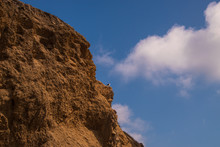 Rugged Jagged Brown Cliff Edge With A Seagull On A Ledge. Deep Blue Sky Background With Broken Puffy Clouds
