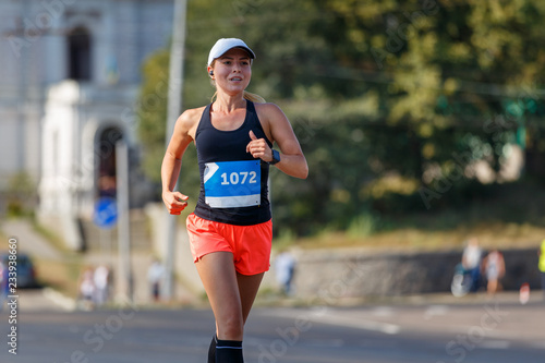 Young sporty woman running in marathon competition Poster Mural XXL