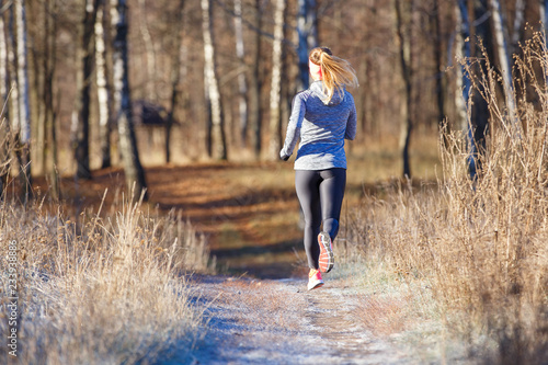 Poster Glisse hiver Rear view of young running woman in winter park