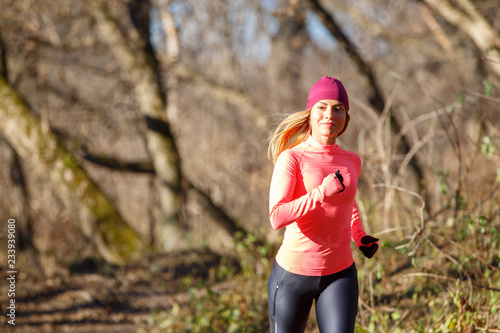 Young woman jogging on trail in autumn park