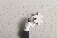 Man Placing The Last Puzzle Piece