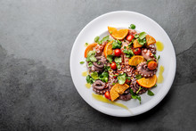 Whole Octopus Salad With Orange, Tomatoes And Cress Salad On White Plate. Top View