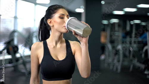 Obraz na płótnie Sporty woman drinking protein shake after workout, muscle gain nutrition, health