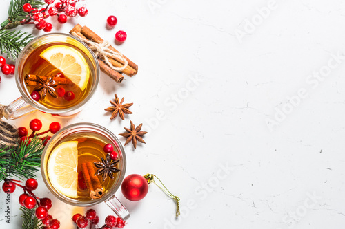 Winter hot tea with fruit, berries and spices on white table.