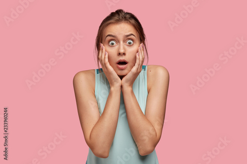 Fototapeta  Scared bugged eyed European woman keeps both hands on cheeks, opens mouth widely, cant believe in shocking news, dressed in casual clothes, isolated over pink background