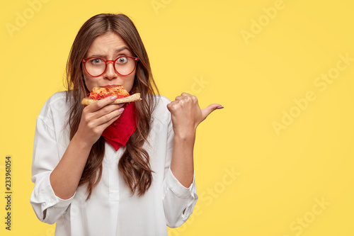 Horizontal shot of surprised female eats tasty slice of pizza, dressed in fashionable clothes, indicates with thumb, invites you to pizzeria, isolated over yellow studio wall. People and nutrition