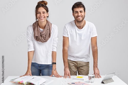 Photo of glad young female and male students lean at table, stand at desktop, learn information, use books and tablet, isolated over white background, solve issues, have brainstroming session