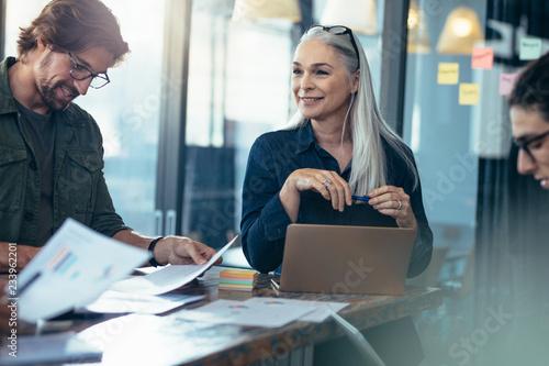 Obraz Business team analyzing financials documents in a meeting - fototapety do salonu
