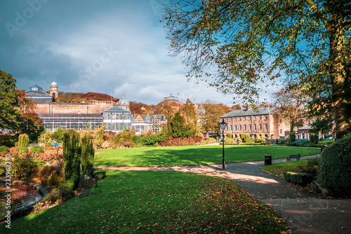 Fotomural Lovely view of Buxton Park in Autumn, showing the calm pond and beautiful autumnal trees as well as the stone architecture of the town