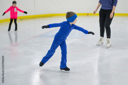 Little boy learning to ice skate. Figure skating school. Young figure skaters practicing at indoor skating rink.