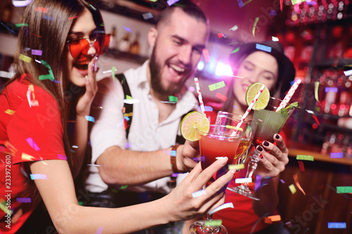 young people celebrate a birthday or Christmas on a nightclub background and salute their confetti