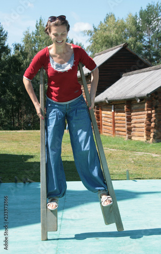 A young athletic girl in sharovarov stands on stilts face with the emotion of joy, uncertainty, caution Slika na platnu