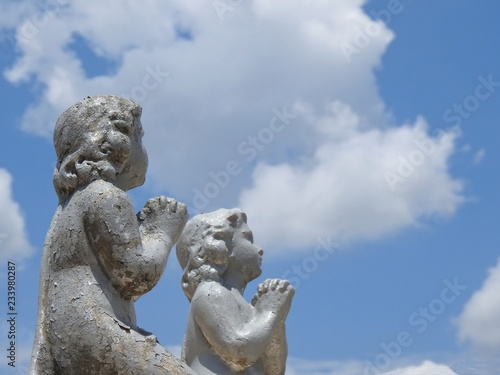 Fotografiet  Scene in a cemetery: two children's stone statues with their hands together, praying