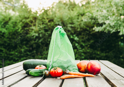 Photo Stands Camping Reusable eco friendly net bag with produce for vegetables and fruits on wooden table outdoors. Buying produce from store and for storage to replace one time use plastic bags.