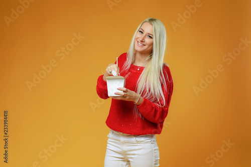 Bright blond woman eating asian fast food from takeaway box with chop sticks, Wok noodles concept
