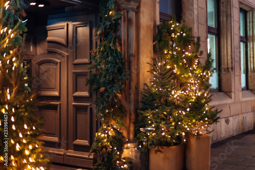 Foto  massive wooden door of the building and Christmas trees are deco