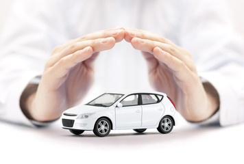 Car insurance. Small white car covered by hands.