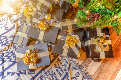 Papiers peints Attraction parc Classic Christmas decorated New year black paper gift box with golden ribbon bow near Christmas tree. Modern dark classical style interior design apartment. Christmas eve at home