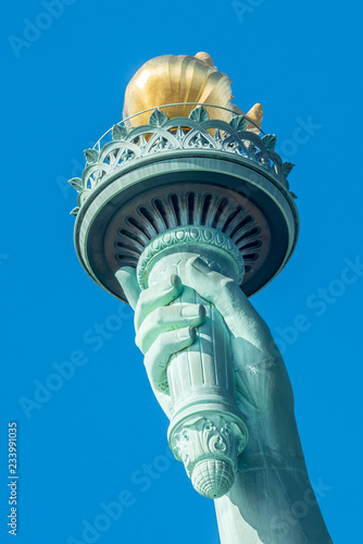 Tuinposter New York City Detail of Statue of Liberty against blue sky in New York City
