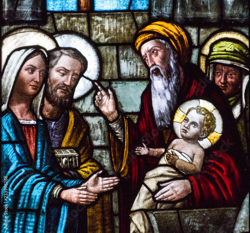 Spoed Fotobehang Stained Casorate Primo, Italy. 2017/12/8. A stained glass window depicting Feast of the Presentation of Our Lord Jesus and the the Purification of the Blessed Virgin Mary in the church of San Vittore Martire.