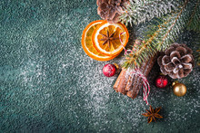 Christmas Green Background. Composition With Dry Oranges And Cinnamon Sticks