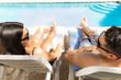 Lovers Sunbathing At Poolside During Honeymoon