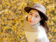 Aerial View Portrait Of Young Chinese Woman In Fashionable Clothes With Golden Autumn Leaves Background In Park, Looking Upwards. Cute Girl In Good Mood Posing In Autumn Day, Enjoying Good Weather.