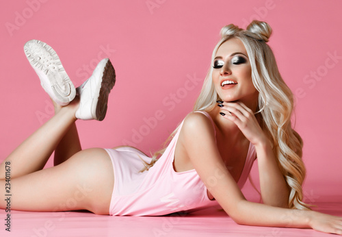 Beautiful ass woman blonde lying on pink color background Canvas Print