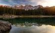 Sunset at Carezza lake with beautiful reflections of dolomites mountains