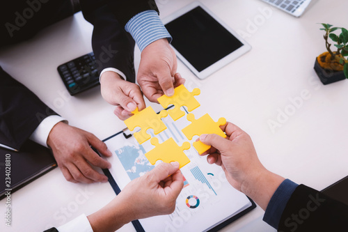 Fototapety, obrazy: Business people assembling jigsaw puzzle with reports graphs and charts on wood table. Teamwork meeting successful workplace strategy concept.