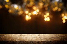 Rustic Wooden Table In Front Of Glitter Black And Gold Bokeh Lights.