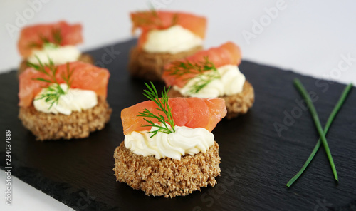 Photo Smoked salmon canapes with cheese cream and dill on brown bread over black slate