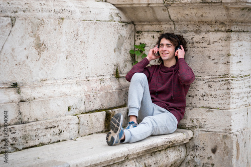 Handsome young man listening to music with headphones on his head. Young man relaxing in front of stone wall