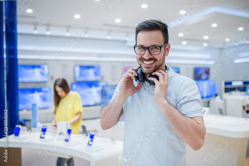 Photo Stands Music store Happy man posing with earphones in tech store. Technology shopping concept.