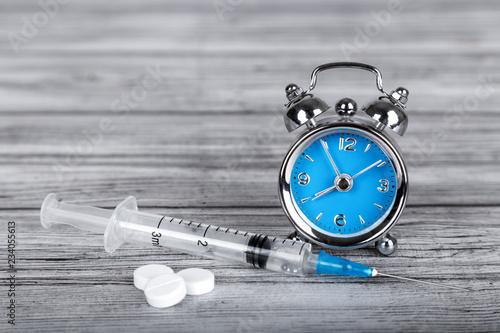 Fotografie, Obraz  Time heals concept. Alarm clock with pills and syringe