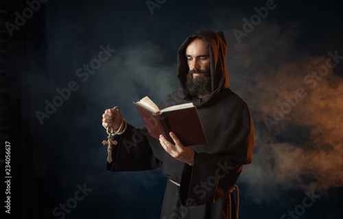 Photo Medieval monk praying with book in church
