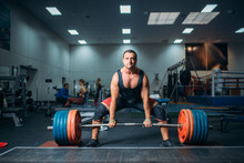 Male Weightlifter Prepares To Pull Heavy Barbell