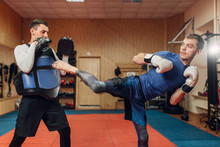 Kickboxer Practicing Kicking With Personal Trainer