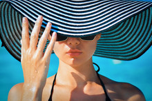Portrait Of A Girl In Glasses And A Hat On A Tropical Beach