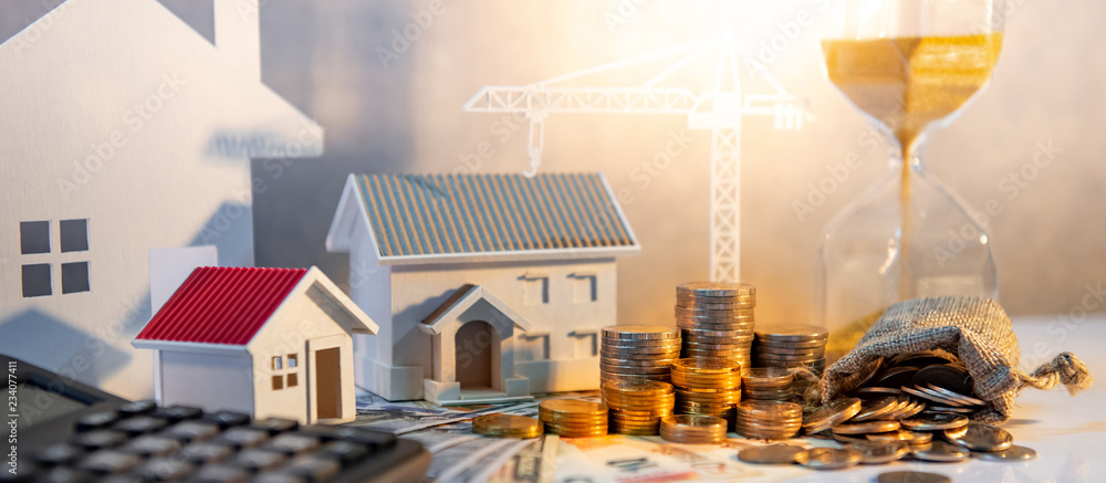 Fototapeta Real estate or property development. Construction business investment concept. Home mortgage loan rate. Coin stack on international banknotes with calculator, house and crane models on the table.