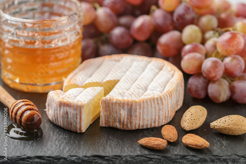 Delicatessen soft fragrant cheese with mold, honey, almonds and red grapes on a black slate plate. Snacks for gourmets