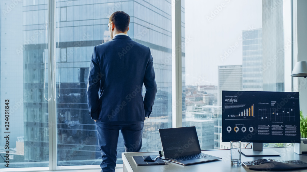 Fototapeta Confident Businessman in a Suit Contemplating Business Deal in His Office, Looking out of the Window. Window Has Panoramic View on Big City Business District.