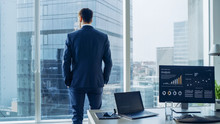Confident Businessman In A Suit Contemplating Business Deal In His Office, Looking Out Of The Window. Window Has Panoramic View On Big City Business District.