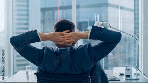 Fototapety, obrazy: Back View of Confident Businessman Sitting at His Desk and Stretches. He's Fatigued and so Tired. Successful Corporate Man Doing Important Job. Modern Office Environment Has Window with Big City View.